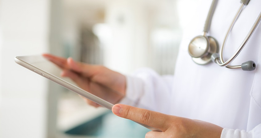 person working in healthcare is using a tablet to submit PHI data in a HIPAA compliant form